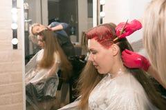 Żeński fryzjer maluje girl's włosianych z muśnięciem przed lustrem w hairdresser's salonie, obraz stock