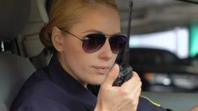 Żeński funkcjonariusz policji akceptuje pojawienia się wezwanie, wymienia informację, praca zespołowa zbiory
