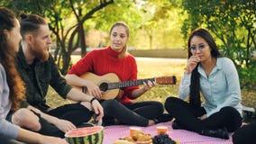 Żeński gitarzysta bawić się gitarę dla radosnych przyjaciół siedzi na koc na gazonie w miasto parku podczas gdy faceci i dziewczy zbiory