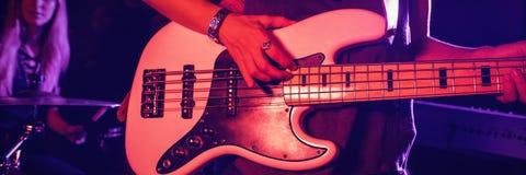 Żeński gitarzysta bawić się gitarę z doboszem w klubie nocnym obraz royalty free