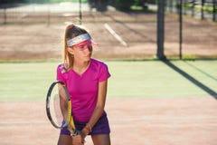 Żeński gracz w tenisa koncentruje i skupia się na jej forehand grą podczas szkolenia na plenerowym sądzie przy zmierzchem obrazy stock