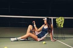 Żeński gracz w tenisa siedzi w sądzie i trzyma bawić się rakietę Obraz Stock