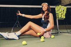 Żeński gracz w tenisa siedzi w sądzie i trzyma bawić się rakietę Fotografia Stock