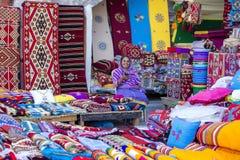 Żeński handlowiec przy Souq Waqif rynkiem w Doha, z multicolour dywanami, kilimami i innymi rzeczami, Qatar dauhańskiej zdjęcie stock