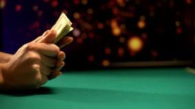 Żeński hazardzista trzyma dolarowych banknoty, światła błyska na tle, kasyno zdjęcie royalty free