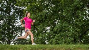 Żeński jogger na śladzie między drzewami obraz royalty free