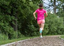 Żeński jogger na śladzie między drzewami obraz stock