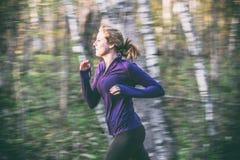 Żeński jogger w natura lasowym śladzie tło plama zamazywał chwyta frisbee doskakiwania ruch zdjęcia stock
