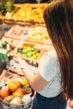 Żeński klient przeciw owocowej sekci w sklepie spożywczym zdjęcia royalty free