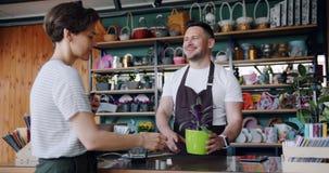 Żeński klient robi zapłacie z smartphone w kwiatu sklepu kupienia houseplant zbiory wideo