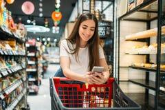 Żeński klient używa telefon komórkowego w supermarkecie obraz stock