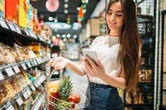 Żeński klient używa telefon komórkowego w supermarkecie zdjęcia royalty free