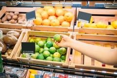 Żeński klient wybiera owoc w sklepie spożywczym zdjęcia royalty free
