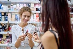 Żeński konsultant pomaga z wyborowym klientem w kosmetykach robi zakupy fotografia stock