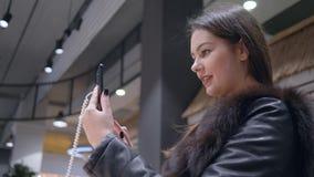 Żeński kupujący w futerek ubraniach wybiera i badający nowożytnego smartphone w elektronika sklepie zbiory wideo