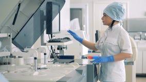 Żeński lab ekspert jest dyrekcyjnym Automatycznym Farmaceutycznym wyposażeniem zbiory