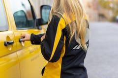 Żeński listonosz od Deutsche Post i DHL na żółty postcar obraz royalty free