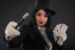 Żeński magik w wykonawcy kostiumu z magicznym różdżki i bawić się ca Zdjęcia Royalty Free