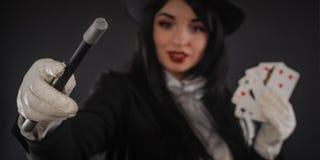Żeński magik w wykonawcy kostiumu z magicznym różdżki i bawić się ca Obrazy Stock