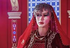 Żeński mannequin w orientalnej aksamit sukni na czerwonym tle obrazy royalty free