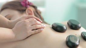 Żeński masażysta taktuje kobiety z powrotem z gorącym kamiennym terapii zwolnionym tempem zbiory wideo