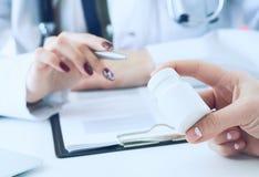 Żeński medycyny lekarki ręki chwyta srebra pióro i punkty słój pigułek wewnątrz - pacjent ręka Potomstwo lekarka opowiada pacjent zdjęcia stock