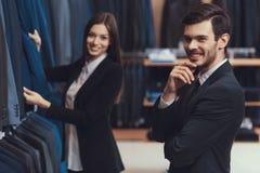 Żeński menswear sklepu konsultant pomaga wybierać kurtkę dla młodego człowieka w kostiumu zdjęcia royalty free