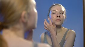 Żeński nastolatek stosuje twarzy śmietankę, trądzika traktowanie, skóry opieki lustrzany odbicie zbiory wideo