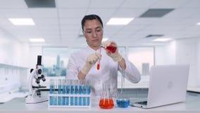 Żeński naukowiec nalewa czerwonego ciecz od kolby w próbną tubkę i robi próbom klinicznym podczas gdy siedzący przy bielem zbiory