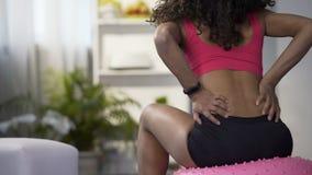Żeński obsiadanie na sprawności fizycznej balowym podnośnym dumbbell, chwyta jej niskiego w bólu z powrotem zbiory wideo