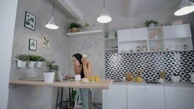 Żeński obsiadanie w kuchni i działaniu na laptopie zdjęcie wideo