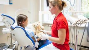 Żeński pediatryczny dentysta daje zabawkarskiego misia jej pacjent Obrazy Royalty Free