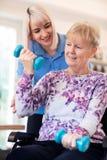 Żeński Physiotherapist Pomaga Starszej kobiety W wózku inwalidzkim Podnosić ręka ciężary zdjęcie stock