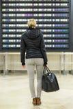 Żeński podróżnika sprawdzać odjazdy wsiada przy lotniskowego terminal sala fotografia stock