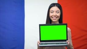 Żeński pokazuje laptop z zieleń ekranem przeciw francuz flagi tłu, nauka zdjęcie wideo