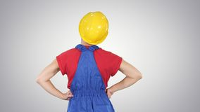 Żeński pracownik budowlany patrzeje coś na gradientowym tle z rękami na biodrach zbiory wideo