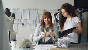 Żeński pracownik krawczyny sklep jest pomiarowymi szat rysunkami z szwalną nicią podczas gdy jej kolega pokazuje ona zbiory wideo