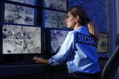 Żeński pracownik ochrony z przenośnym nadajnikiem monitoruje nowożytne CCTV kamery zdjęcie royalty free
