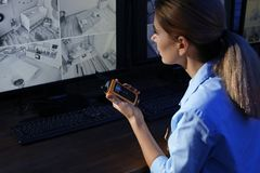 Żeński pracownik ochrony z przenośnym nadajnikiem monitoruje nowożytne CCTV kamery obrazy royalty free