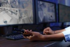 Żeński pracownik ochrony z przenośnym nadajnikiem monitoruje nowożytne CCTV kamery indoors zdjęcia royalty free