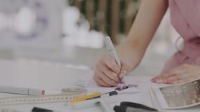 Żeński projektant mody z pięknymi manicure'u rysunku nakreśleniami Mierzy taśmy lub sentimentr, ołówek, markiery na zbiory