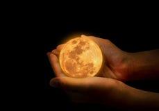Żeński ręka chwyta koloru żółtego księżyc w pełni Obrazy Stock