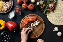 Żeński ręki cięcie ono rozrasta się wokoło kłamstwo składników dla pizzy i pomidory na drewnianej desce na kuchennym stole: warzy Obrazy Stock