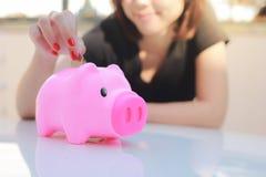 Żeński ręki kładzenia pieniądze w prosiątko banka Fotografia Stock