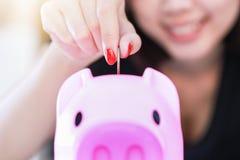 Żeński ręki kładzenia pieniądze w prosiątko banka Obraz Stock