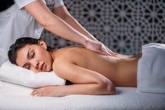 Żeński robi masaż dla czarnej z włosami Azjatyckiej kobiety ma problemy z plecy obrazy stock