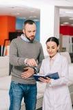 żeński sklepowy asystent w białym żakiecie z notatnika pomaga klientem w wybierać materac obrazy royalty free