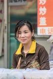 Żeński sprzedawca sprzedaje ulicznego jedzenie na lokalnym rynku, Pekin, Chiny Obraz Stock