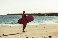 żeński surfingowiec z surfboard odprowadzeniem na plaży blisko zdjęcie stock