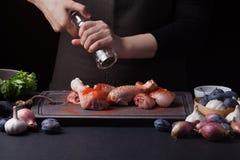 Żeński szef kuchni kropi świeżych surowych kurczaków drumsticks na ciemnym tle z miksturą pieprze Niedaleki kłamstwo fotografia stock